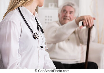 Doctor diagnosing disabled man - Young female doctor...