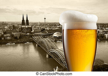 Glass of beer with view of Koeln on background, Germany