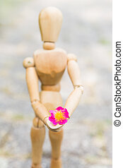 bringing a gift - manikin of wood holding a blossom in the...