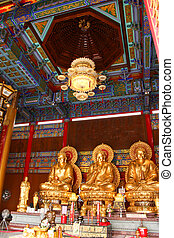 Three buddha sculpture sitting in temple as vertical