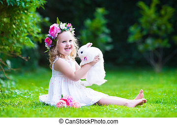 Cute girl playing with real bunny - Little girl with real...