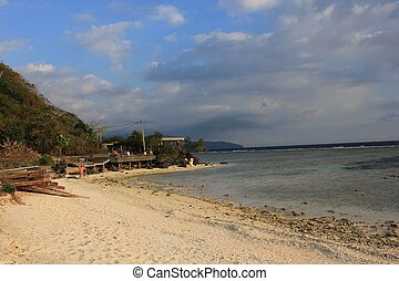 Gili Trawangan coastline at sunset light, with few people in...