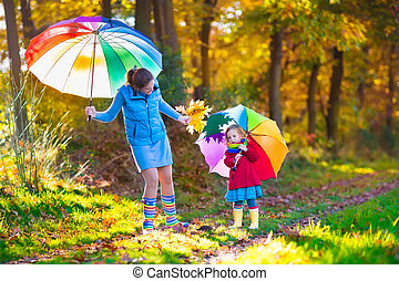 Mother and child walking in autumn park - Mother and...