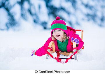 Little girl enjoying a sleigh ride in winter
