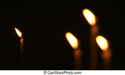 Some burning church candles. - Close up. Changing focus from...