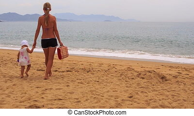 young blonde mother little daughter come to beach lay mat -...