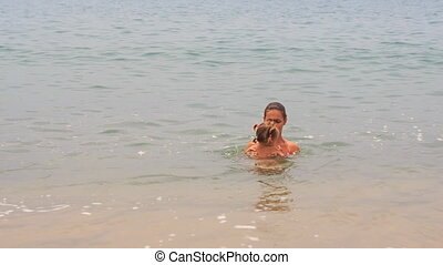 young mother swims play with little daughter in shallow sea
