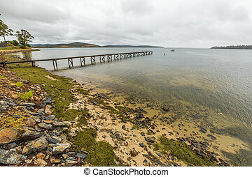 East Coast Tasmania - Cloudy landscape and wooden jetty in...