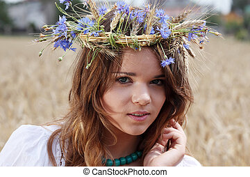 Beautiful young girl in summer field