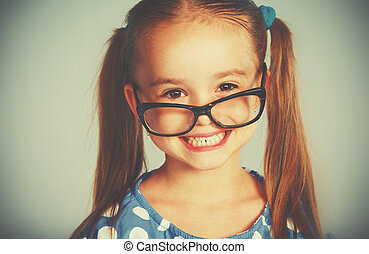 funny smiling child girl in glasses - A funn