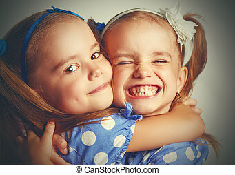 Happy funny twins sisters hugging and laughing - Happy funny...