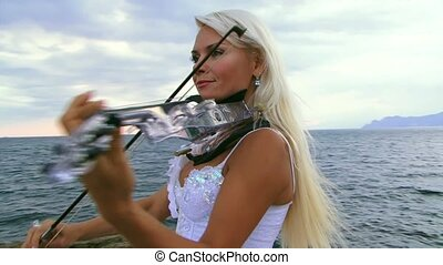 Woman Plays The Violin - Beautiful violinist clad in a...