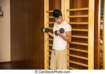 Attractive young man working out with dumbbells at gym