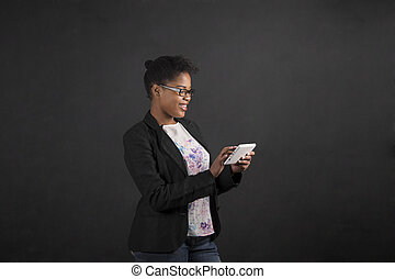 African woman with tablet on blackboard background - South...