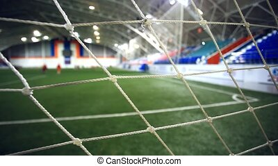view through focused net. Blurred players play on Soccer field of stadium with light on background have a bokeh