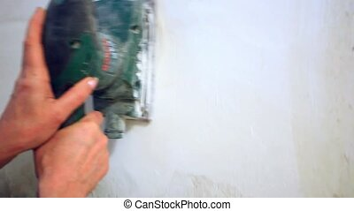 plastering female hand sanding the plaster in white wall....