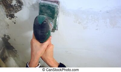 plastering female hand sanding the plaster in white wall...