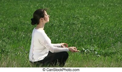 Woman Engaged In Meditation - A beautiful girl sitting in...