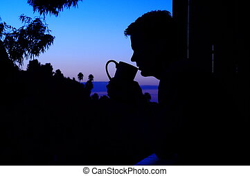 PreDawn Sunrise Silhouette of Man Drinking Coffee on Cabin Balcony Overlooking Hill Vista