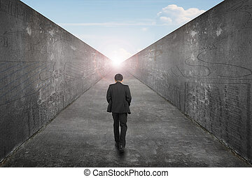Businessman walking one way road toward exit sun sky view -...