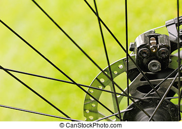 close up of bicycle disc brakes on green grass background