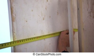 Worker hands measuring plaster wall for further wallpapering...