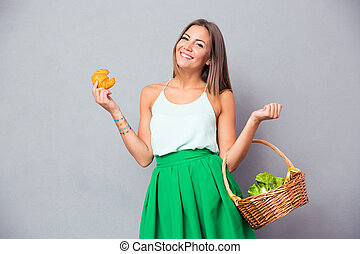 Woman holding basket with vegetables and bagel - Portrait of...