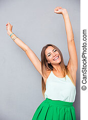Smiling woman with raised hands up