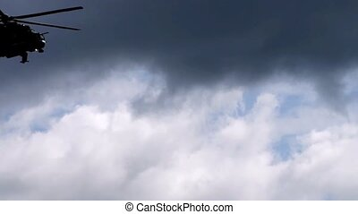 Two military helicopters flying in cloudy sky