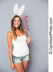 Girl with rabbit ears holding lollipop - Smiling young girl...