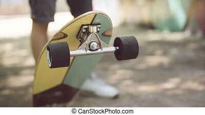 Man tipping up a skateboard with his foot with the wheels...