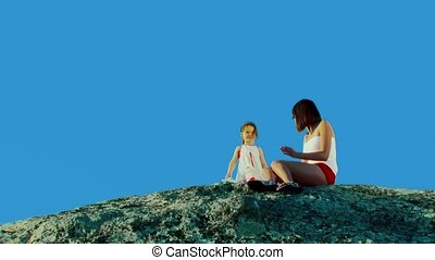 Surprise - Two girls sit on a rock and talk.