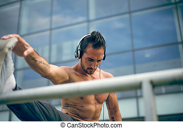 Heavy workout - Young man listening to the music and...