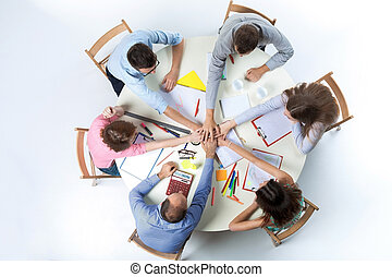 Top view. United hands of business team on workspace...