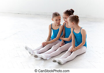 Three little ballet girls sitting and talking together -...