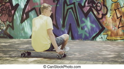 Man Sitting on Longboard and Looking Into Distance - Rear...