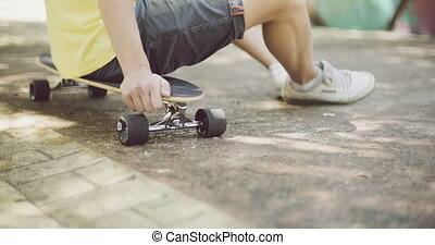 Man sitting on his skateboard - Close up torso view of a man...