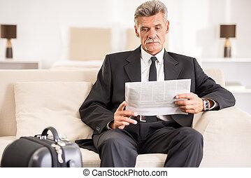 Business Trip - Mature business man reading a newspaper...