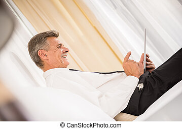 Business Trip - Businessman using his digital tablet and...