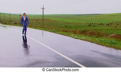 Walking - It is raining. The young man goes on the centre of...