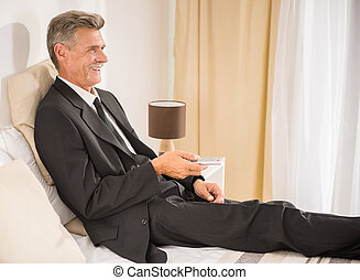 Business Trip - Businessman in suit lying on bed and...