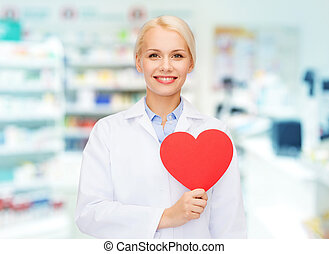 woman pharmacist with heart at drugstore - medicine,...