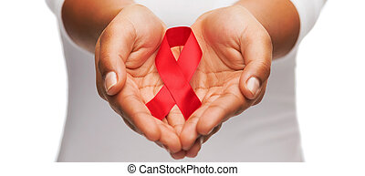 hands holding red AIDS awareness ribbon - healthcare and...