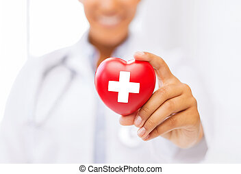 female doctor holding heart with red cross symbol -...