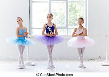 Three little ballet girls in tutu and posing together -...