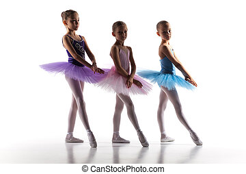 Three little ballerinas dancing in dance studio - The...