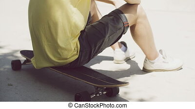 Boy sitting on a skateboard outdoors - Low angle view of the...