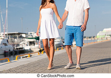 close up of couple holding hands and walking - love, travel,...