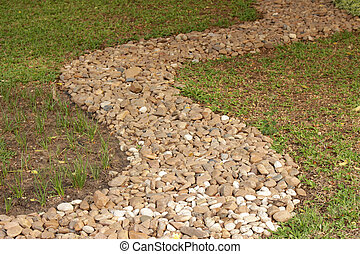 Stone wash pebble path on green grass