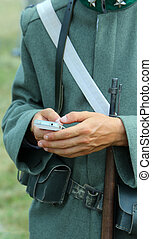 Rifle and Smartphone of a soldier during reenactment of a...